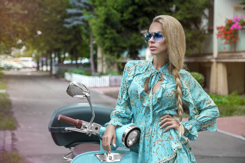 Attractive woman riding on motorbike in street, summer vacation style, traveling, smiling, happy, having fun, stylish outfit, royalty free stock photography