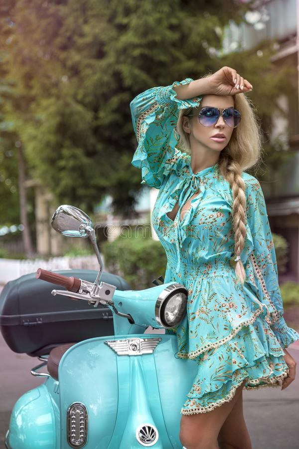 Attractive woman riding on motorbike in street, summer vacation style, traveling, smiling, happy, having fun, stylish outfit, stock photography