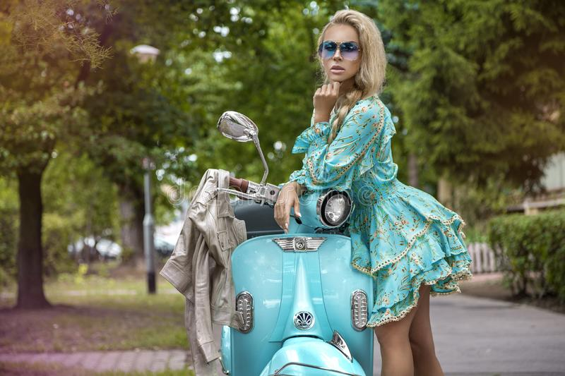 Attractive woman riding on motorbike in street, summer vacation style, traveling, smiling, happy, having fun, stylish outfit, royalty free stock photos