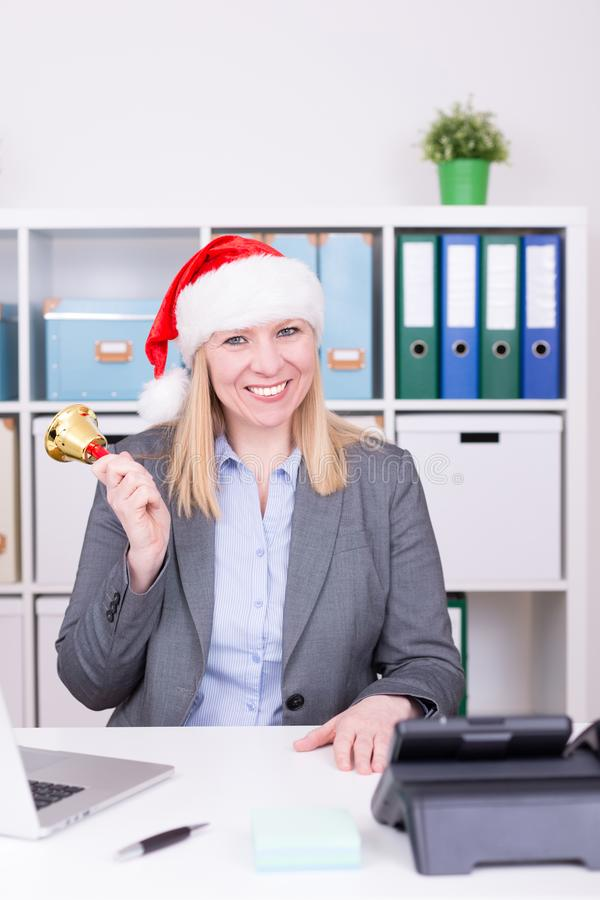 Attractive woman is ringing the bell at christmas time. Business, christmas and new year celebration concept stock images