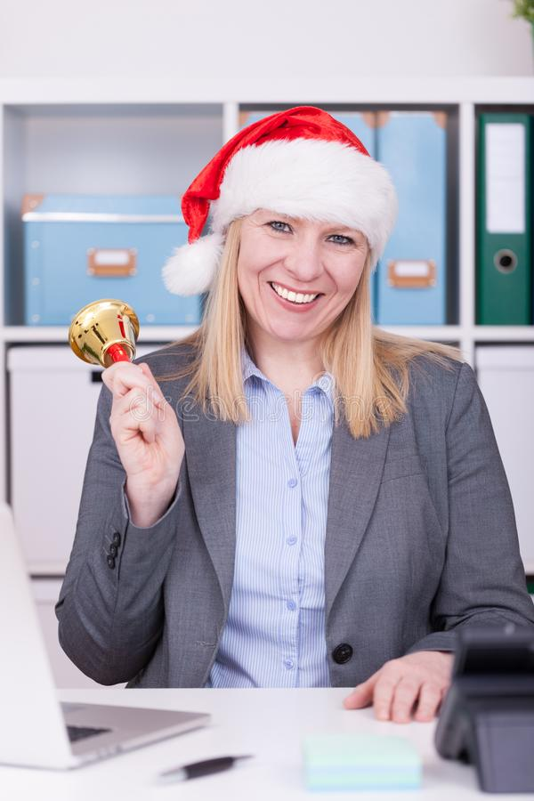 Attractive woman is ringing the bell at christmas time. Business, christmas and new year celebration concept royalty free stock photo