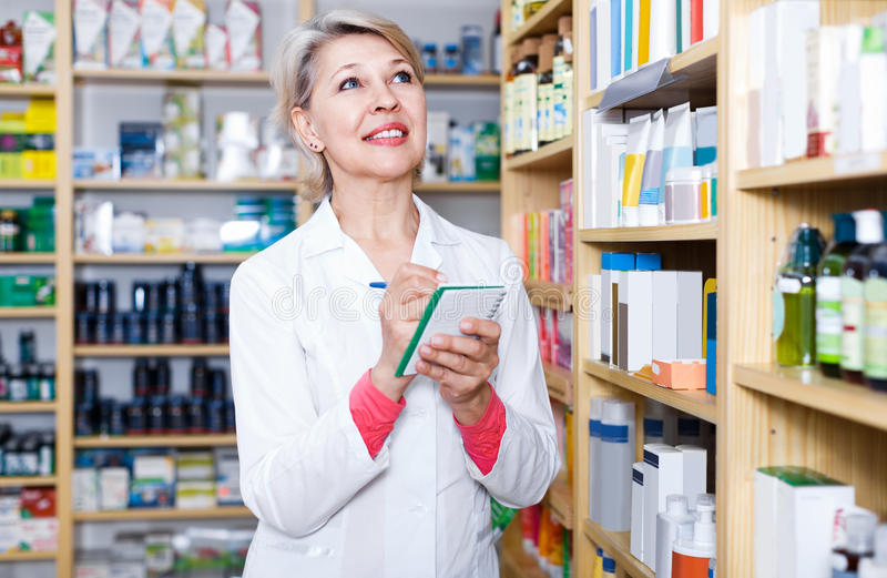 Attractive woman seller writing down care products in shop. Attractive woman seller writing down assortment of care products in shop stock photography