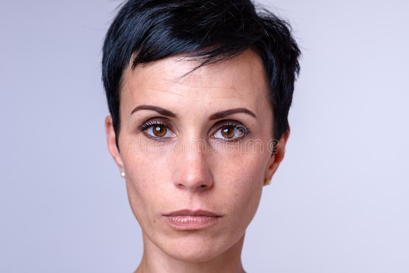 Attractive woman with big brown eyes. Attractive woman with a short modern hairstyle and big brown eyes looking solemnly at the camera, head shot over grey royalty free stock photography
