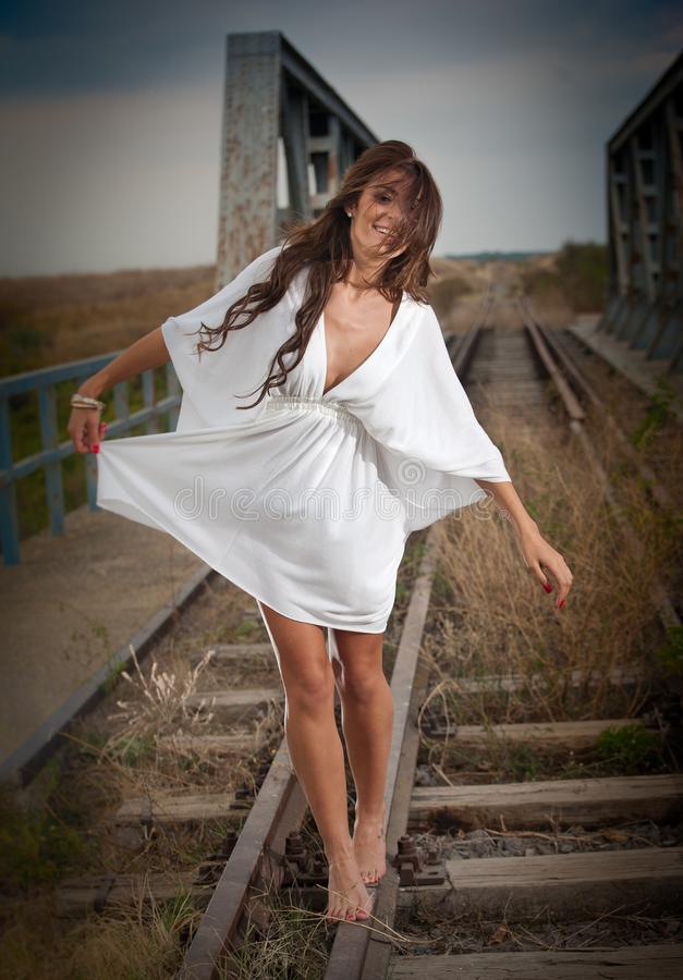 Attractive woman with short white dress and long hair standing on the rails with bridge in background. Fashion girl with sex royalty free stock images