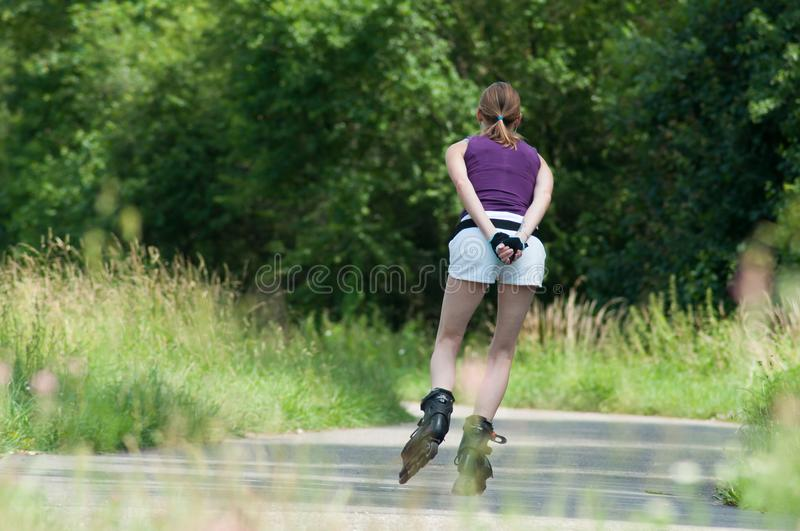 Attractive woman in shorts drives roller skates in border forest royalty free stock image