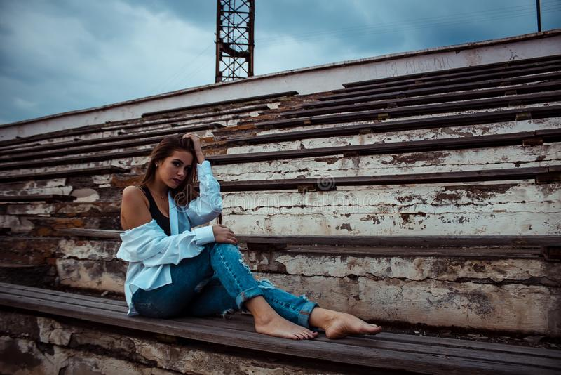 Attractive woman sitting with bare feet in the stadium. She`s wearing a shirt and jeans royalty free stock photo