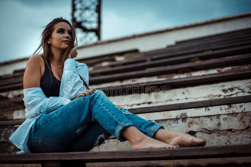 Attractive woman sitting with bare feet in the stadium. She`s wearing a shirt and jeans royalty free stock images