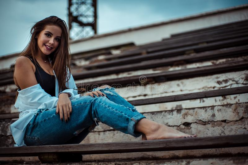 Attractive woman sitting with bare feet in the stadium. She`s wearing a shirt and jeans royalty free stock image