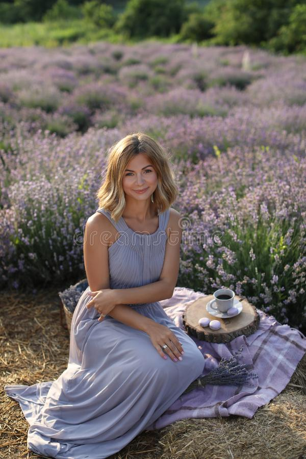 attractive woman sitting on blanket at picnic in violet lavender stock photos