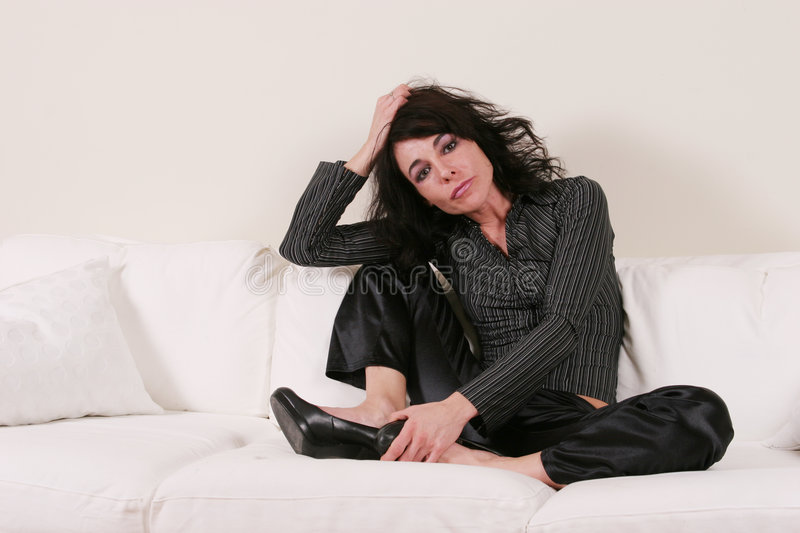 Attractive woman sitting on a couch stock photo