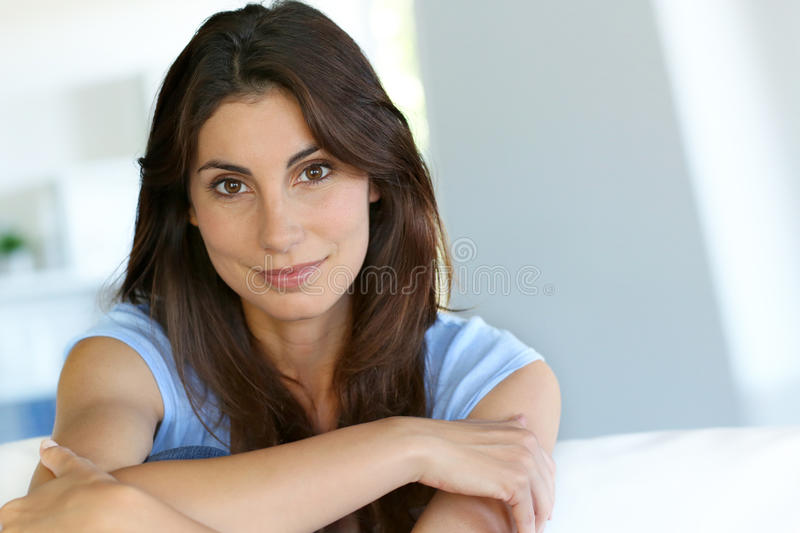 Attractive woman sitting on couch royalty free stock image