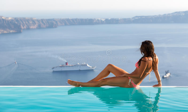 Attractive woman sitting at the edge of an infinity pool and watching the scenery. In Santorini royalty free stock images