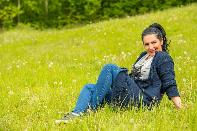 Attractive woman in nature. Attractive woman sitting on green grass in nature royalty free stock image
