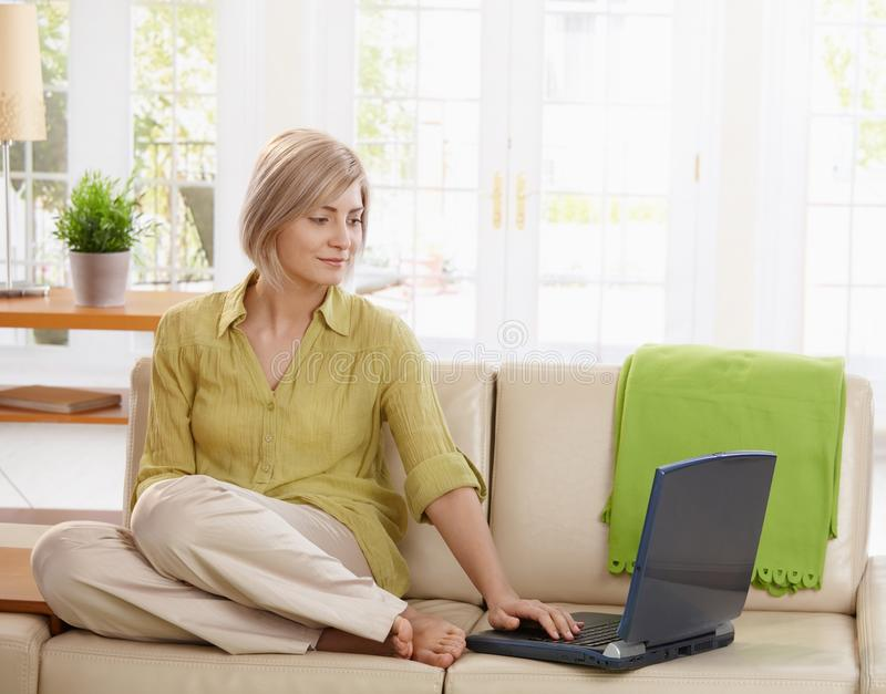 Woman using computer on couch. Attractive woman sitting on living room couch looking at laptop computer stock image