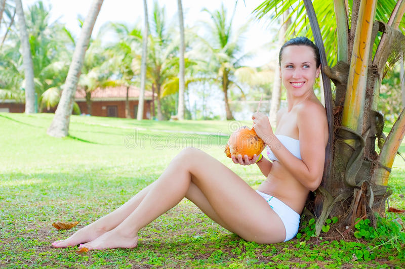 Attractive woman sitting near the palm