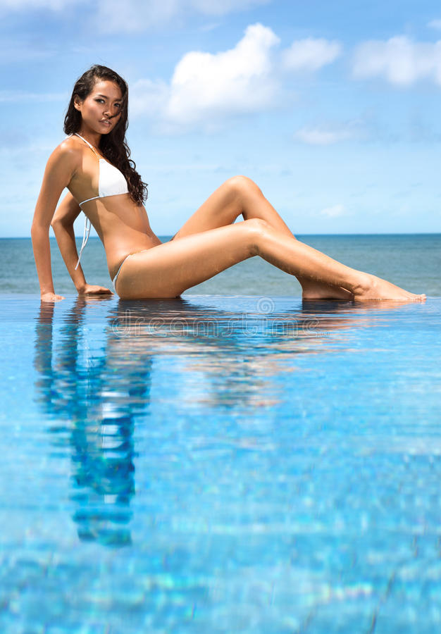 Attractive woman sitting on the rim of the swimming pool with th stock image