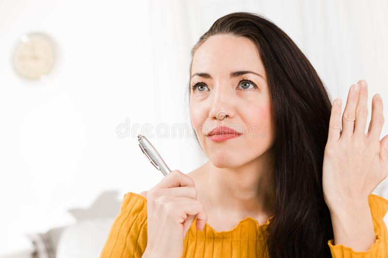 Attractive woman sitting and white table and handwriting with pe stock photo
