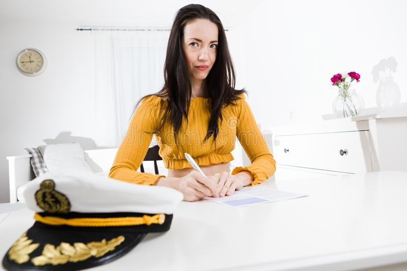 Attractive woman sitting and white table and writing with pen - Captain cap stock images