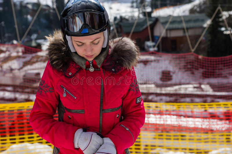 Attractive woman in ski suit, with helmet and ski goggles putting on gloves in a ski-resort stock image