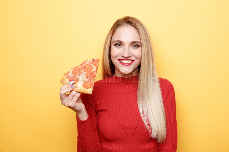 Attractive woman with slice of cheese pizza isolated over the pink background. stock photography