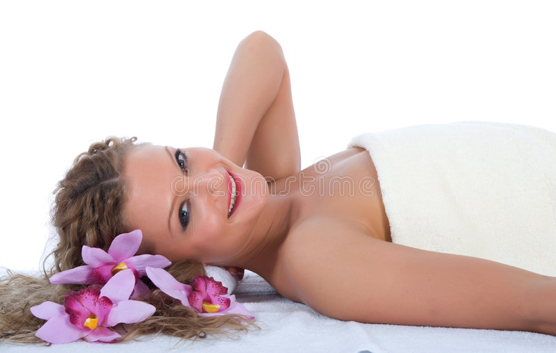 Attractive woman at spa. Attractive woman in towel reclining on her back, at spa stock photography