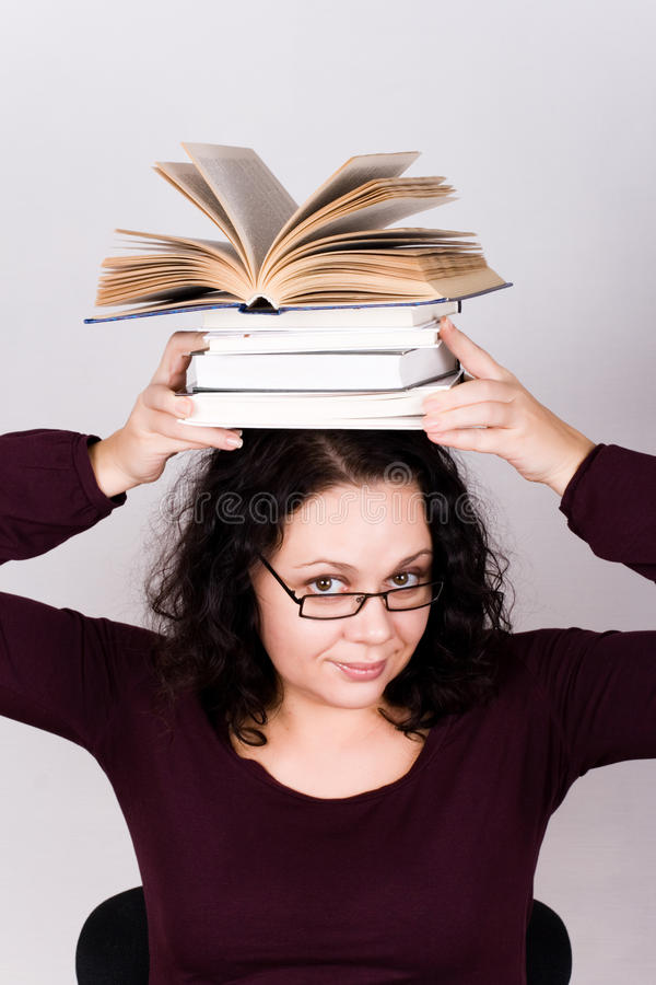 Attractive woman with stack of books royalty free stock images