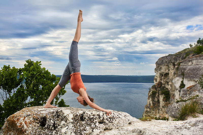 Attractive woman standing on the rock and doing yoga exercises above river. Young woman in the t-shirt, leggings and barefoot. Horizontal photo. Beautiful sky stock photo