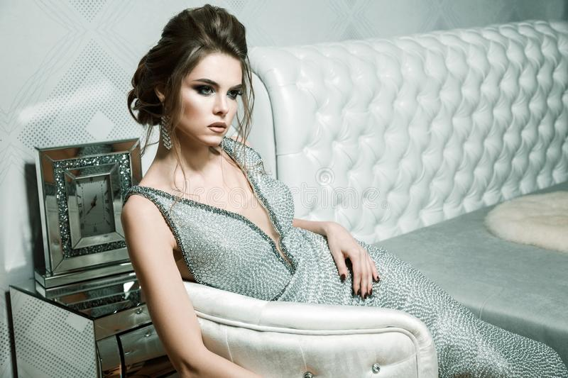 attractive woman with stylish hairdo and bright makeup in evening dress , hairstyle and hollywood makeup sitting on white stock photos