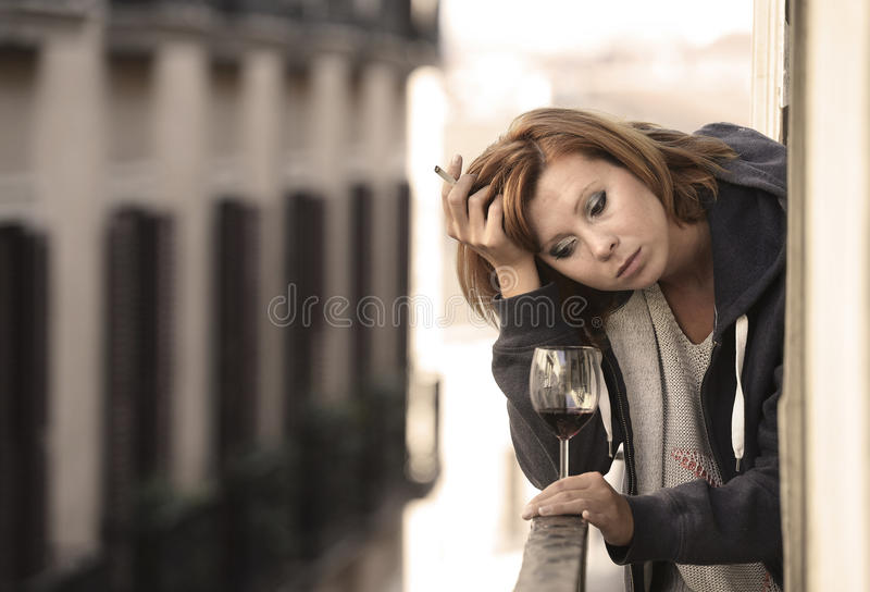 Attractive woman suffering depression and stress outdoors at the balcony. Young attractive woman suffering depression and stress smoking drinking glass of wine stock images