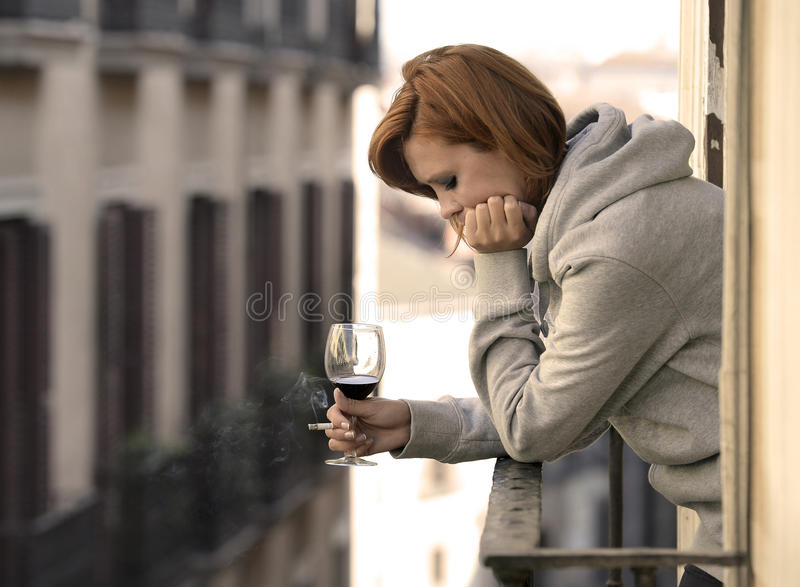Attractive woman suffering depression and stress outdoors at the balcony. Young attractive woman suffering depression and stress smoking drinking glass of wine royalty free stock images