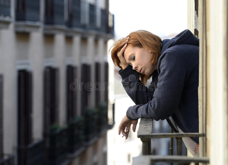 Attractive woman suffering depression and stress outdoors at the balcony. Young attractive woman suffering depression and stress smoking outdoors at the balcony royalty free stock image