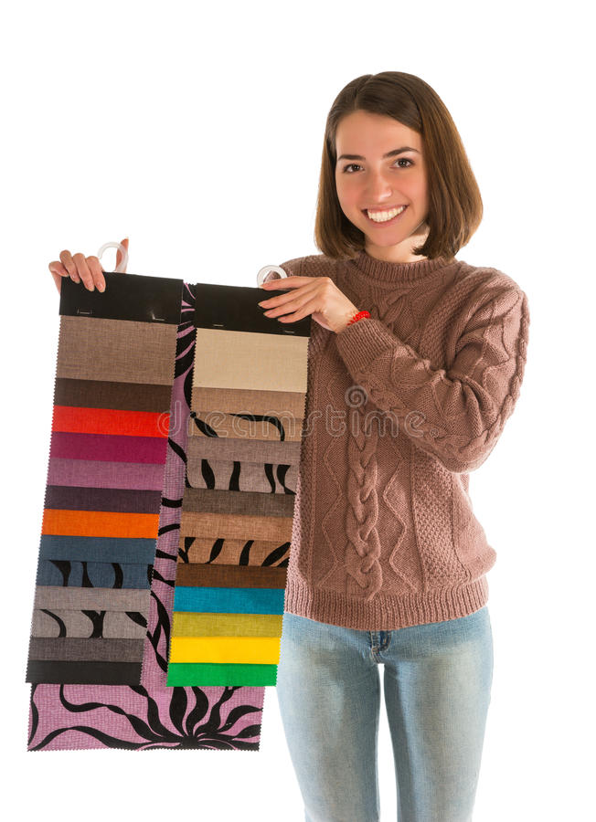 Attractive woman in sweater holding fabric swatches. Isolated on white background royalty free stock image