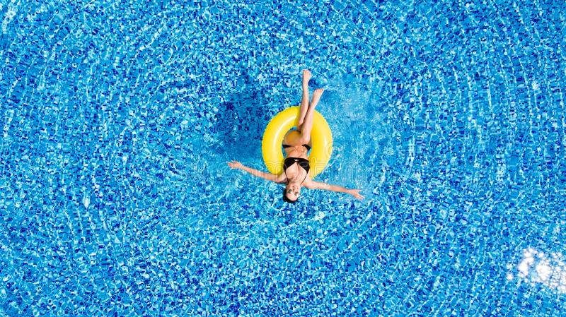 Attractive woman in swimsuit in the yellow rubber ring in the swimming pool from above. Woman in swimsuit in the yellow rubber ring in the swimming pool from royalty free stock image