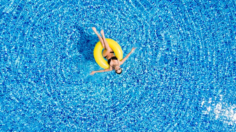 Attractive woman in swimsuit in the yellow rubber ring in the swimming pool from above. Woman in swimsuit in the yellow rubber ring in the swimming pool from stock photo