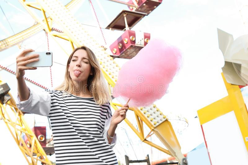 Attractive woman taking selfie with cotton candy. In amusement park royalty free stock photos