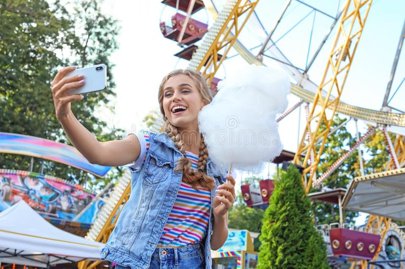 Attractive woman taking selfie with cotton candy. In amusement park stock photos