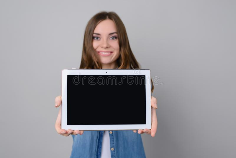 Attractive woman with toothy smile showing digital tablet with black blank touchscreen. The woman is isolated on grey background p royalty free stock image