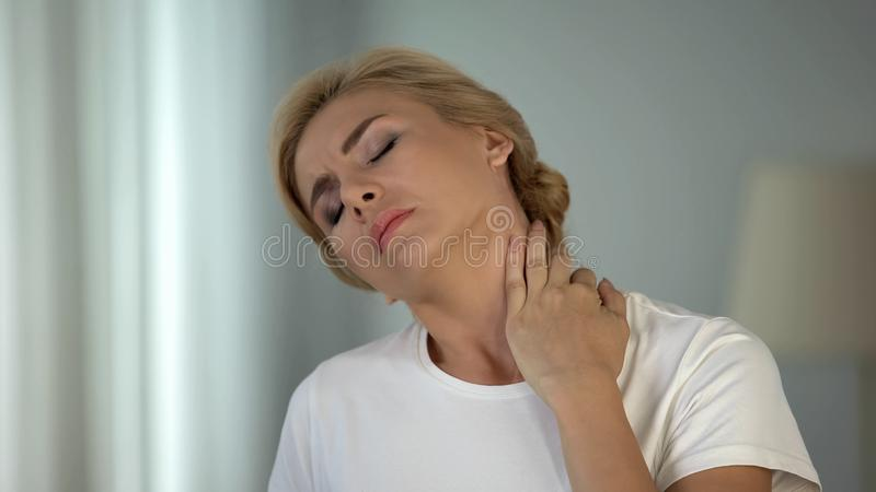 Attractive woman touching and massaging her painful neck, health problems. Stock photo stock images