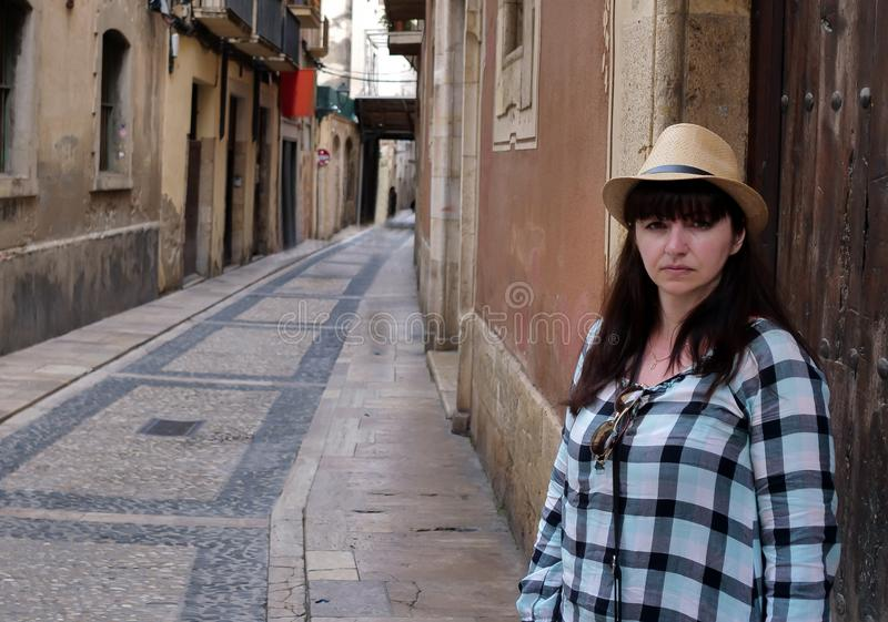 Attractive young woman tourist in a hat stands on a narrow European street stock photos