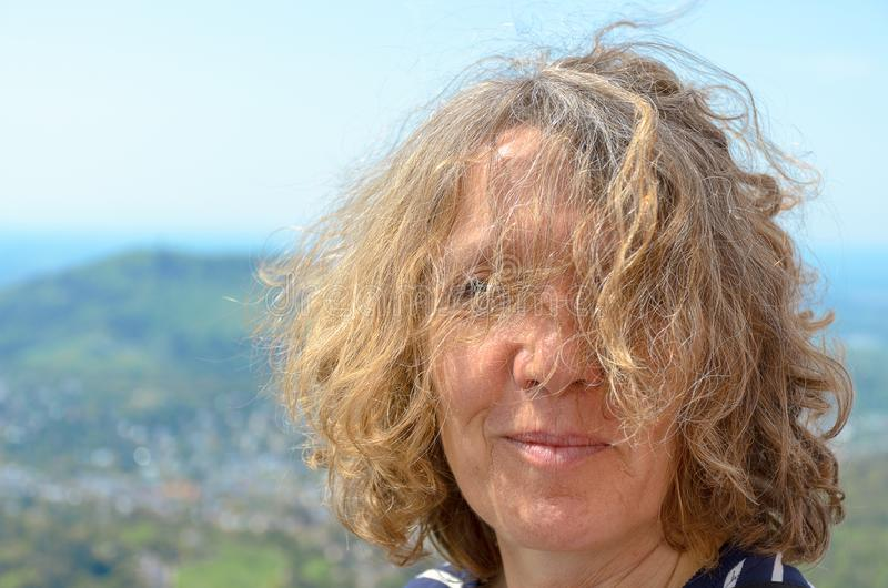 Attractive woman with tousled curly hair. Blowing across her face in a close up head shot outdoors in a mountainous landscape stock photo