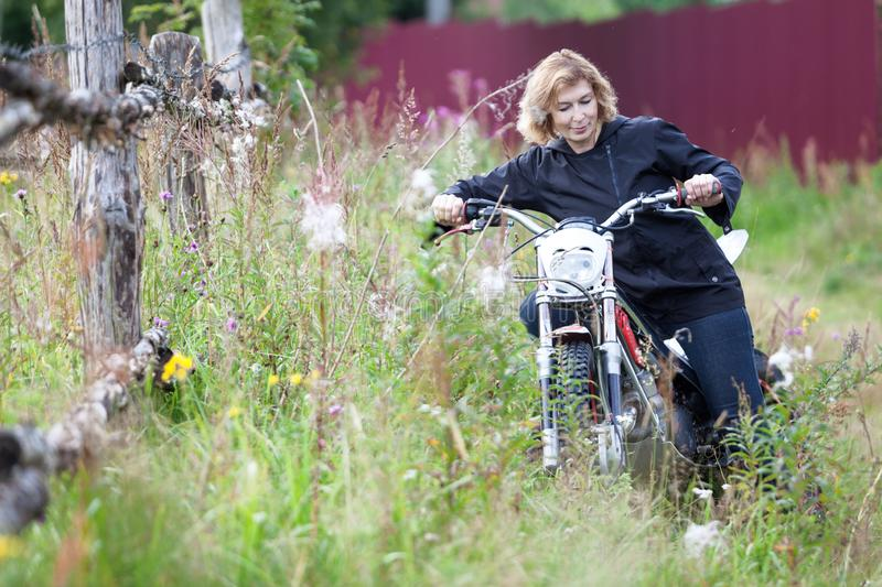 Attractive woman trying to ride the motocross motorcycle in high grass, holding the steering wheel and pushing the bike stock photo
