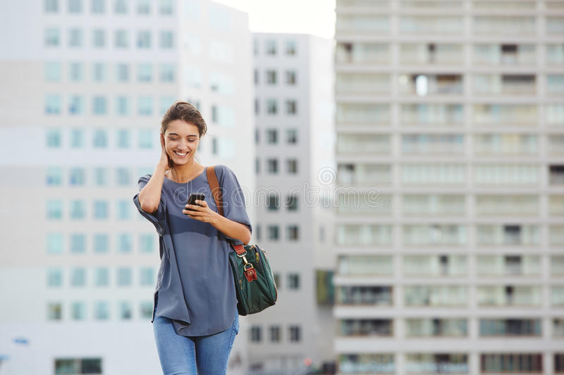 Attractive woman using cell phone outdoors. Portrait of attractive young woman walking outside and reading text message on cell phone stock images