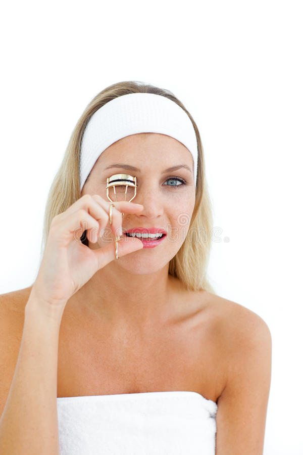 Attractive woman using an eyelash curler. Isolated on a white background stock photo