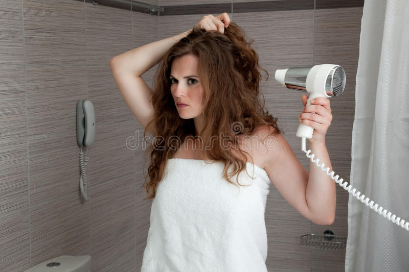 Attractive woman using fen in bathroom. Dressed in towel beautiful woman using fen at modern bathroom royalty free stock photos
