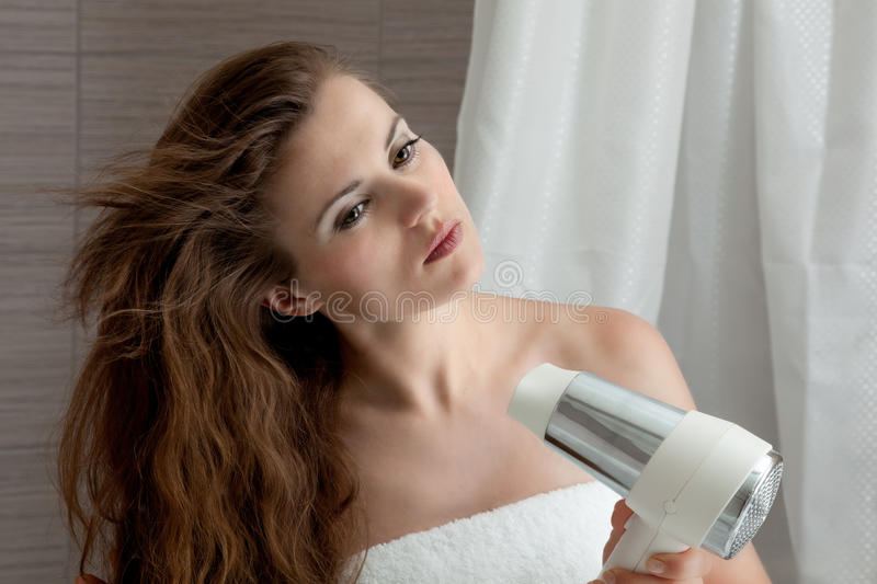 Attractive woman using fen in bathroom. Dressed in towel beautiful woman using fen at modern bathroom stock photo