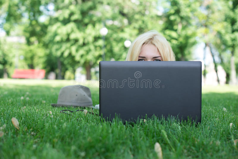 Attractive woman using laptop in the park lying. On the green grass royalty free stock photo