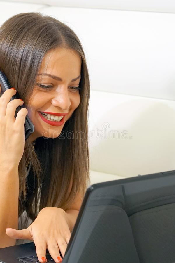 Attractive woman using a mobile phone and a laptop computer lying down in the intimacy of home stock images