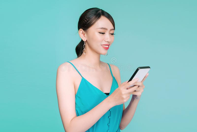 Attractive woman using text messaging feature on her portable device in studio.  stock photo