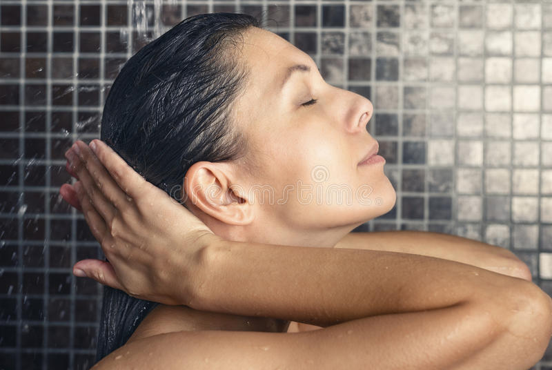 Attractive woman washing her hair in the shower royalty free stock images