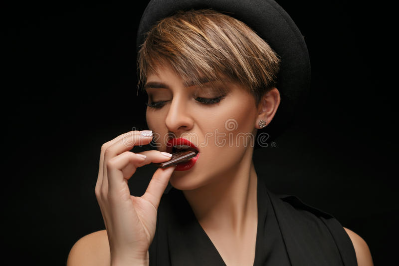 Attractive woman wearing black hat and classical t-shirt eat chocolate in a dark background. royalty free stock image